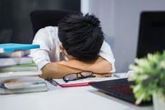 Estudiante joven que se sienta y que duerme en el escritorio con el libro y el ordenador portátil Imagen de archivo