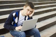 Estudiante joven que trabaja en una computadora portátil Imagen de archivo libre de regalías
