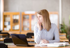 Estudiante joven que usa el ordenador en una biblioteca Mirada lejos Imágenes de archivo libres de regalías