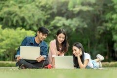 Estudiante joven que usa el ordenador portátil junto en el parque Fotografía de archivo