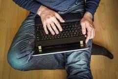 Estudiante joven que usa el ordenador portátil y sentándose en el piso de madera Imágenes de archivo libres de regalías