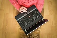 Estudiante joven que usa el ordenador portátil y sentándose en el piso de madera Foto de archivo