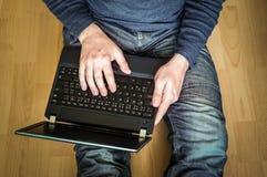 Estudiante joven que usa el ordenador portátil y sentándose en el piso de madera Imagenes de archivo