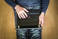 Estudiante joven que usa el ordenador portátil y sentándose en el piso de madera Fotos de archivo