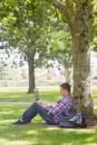 Estudiante joven que usa su ordenador portátil afuera foto de archivo