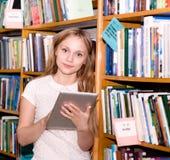 Estudiante joven que usa una tableta en una biblioteca Imagen de archivo libre de regalías