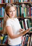 Estudiante joven que usa una tableta en una biblioteca Imagenes de archivo