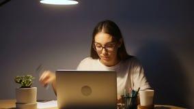 Estudiante joven serio que estudia usando el ordenador portátil de la PC, mujer que trabaja tarde metrajes