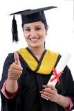 Estudiante joven sonriente de la graduación que hace gesto del thumbsup Imagen de archivo libre de regalías