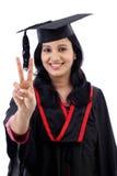 Estudiante joven sonriente de la graduación que hace gesto del thumbsup Fotografía de archivo