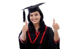 Estudiante joven sonriente de la graduación que hace gesto del thumbsup Fotografía de archivo libre de regalías