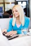 Estudiante joven sonriente en café con el ordenador portátil Imagen de archivo libre de regalías