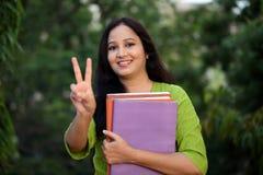 Estudiante joven sonriente que hace la muestra de la victoria Imagen de archivo libre de regalías