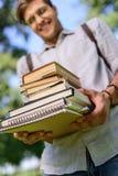 Estudiante joven sonriente que sostiene la pila de libros fotografía de archivo libre de regalías