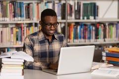 Estudiante joven Using His Laptop en una biblioteca imagenes de archivo