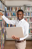 Estudiante joven Using His Laptop en una biblioteca foto de archivo libre de regalías