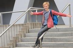 Estudiante juguetón que resbala abajo de la barandilla en la escalera Imagen de archivo libre de regalías