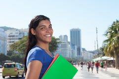 Estudiante latino feliz con el pelo oscuro largo en la ciudad Imagenes de archivo
