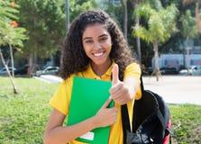 Estudiante latinoamericano con el pelo oscuro largo que muestra el pulgar Foto de archivo