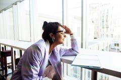 Estudiante linda joven del inconformista que se sienta en café con el cuaderno con referencia a Foto de archivo