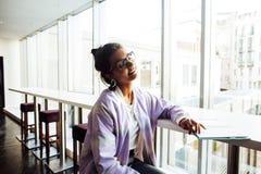 Estudiante linda joven del inconformista que se sienta en café con el cuaderno con referencia a Imagen de archivo