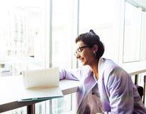 Estudiante linda joven del inconformista que se sienta en café con el cuaderno con referencia a Foto de archivo libre de regalías