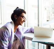 Estudiante linda joven del inconformista que se sienta en café con el cuaderno con referencia a Imagenes de archivo