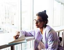 Estudiante linda joven del inconformista que se sienta en café con el cuaderno con referencia a Fotografía de archivo libre de regalías