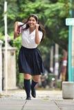 Estudiante linda Running With Notebook foto de archivo