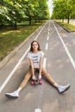 Estudiante lindo de la chica joven que se sienta en un longboard en el camino en un parque con un peinado hermoso y que mira la c Imágenes de archivo libres de regalías