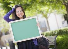 Estudiante lindo Holding Blank Chalkboard de la raza mixta fotografía de archivo libre de regalías