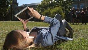 Estudiante lindo que estudia con la tableta en parque metrajes
