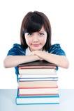 Estudiante lindo que se reclina sobre los libros Foto de archivo