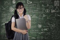 Estudiante lindo que sostiene el ordenador portátil en clase Fotos de archivo libres de regalías