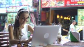Estudiante Listening To Music en el ordenador mientras que estudia almacen de video
