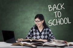 Estudiante listo que usa el ordenador portátil y los libros en clase Imágenes de archivo libres de regalías