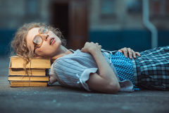 Estudiante loca divertida con los vidrios que mienten en una pila de libros Fotografía de archivo