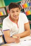 Estudiante masculino adolescente en sala de clase Imagen de archivo libre de regalías