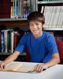 Estudiante masculino adolescente Sitting At Table en biblioteca Imagenes de archivo