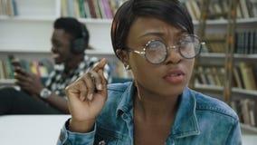 Estudiante masculino africano usando el teléfono elegante mientras que otro estudiante que se prepara a los exámenes metrajes