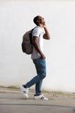Estudiante masculino alegre que camina y que habla en el teléfono celular Imagen de archivo libre de regalías