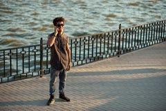Estudiante masculino alegre que habla en el teléfono celular Fotos de archivo