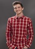 Estudiante masculino amistoso con las manos en los bolsillos que parecen serios Imagenes de archivo