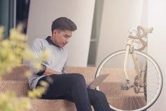 Estudiante masculino asiático que se sienta en las escaleras y que sonríe como lapt del uso Fotografía de archivo libre de regalías
