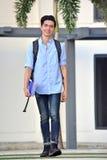 Estudiante masculino asiático Smiling Walking de la universidad foto de archivo