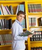 Estudiante masculino With Book Standing contra estante adentro Imágenes de archivo libres de regalías