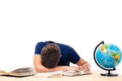 Estudiante masculino cansado que duerme en la tabla Foto de archivo