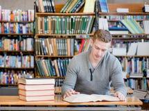 Estudiante masculino con el libro abierto que trabaja en una biblioteca Fotografía de archivo