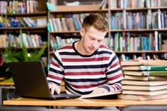 Estudiante masculino con el ordenador portátil que estudia en la biblioteca de universidad Fotos de archivo