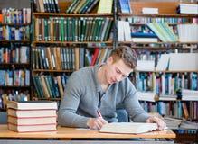 Estudiante masculino con el ordenador portátil que estudia en la biblioteca de universidad Imagenes de archivo